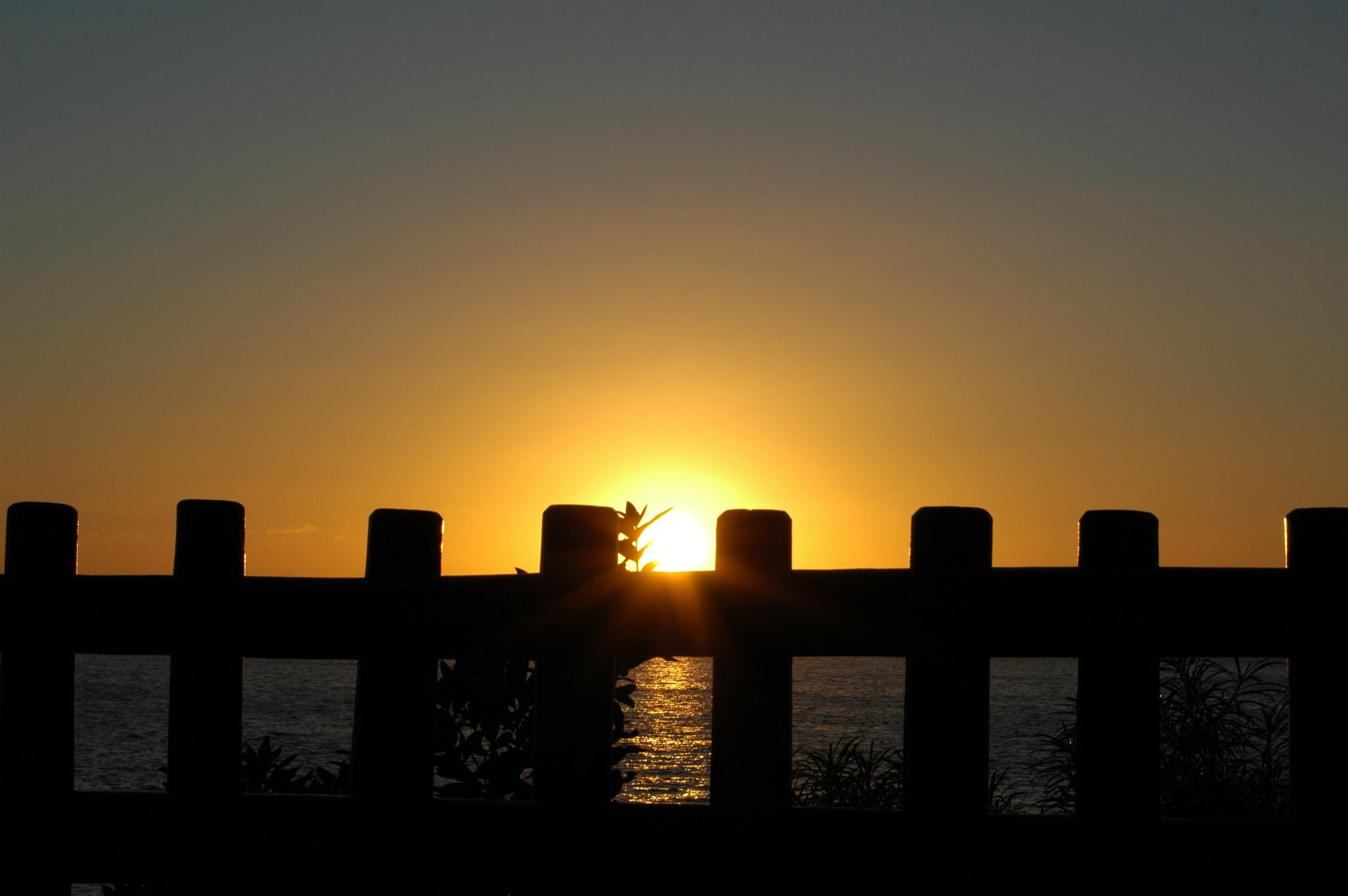 Gate blocking ocean and sunset